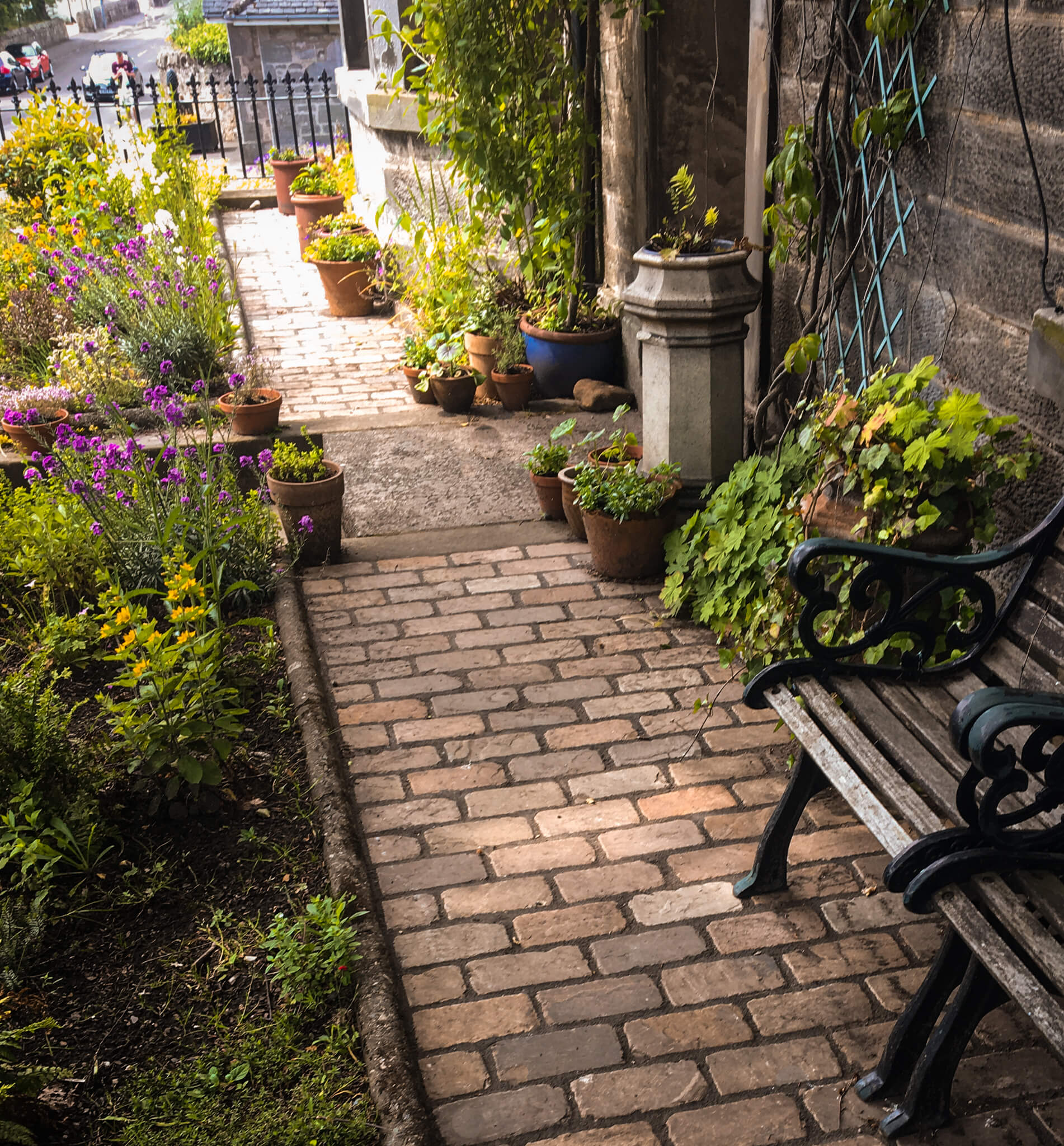 Stone driveway in a garden with a bench