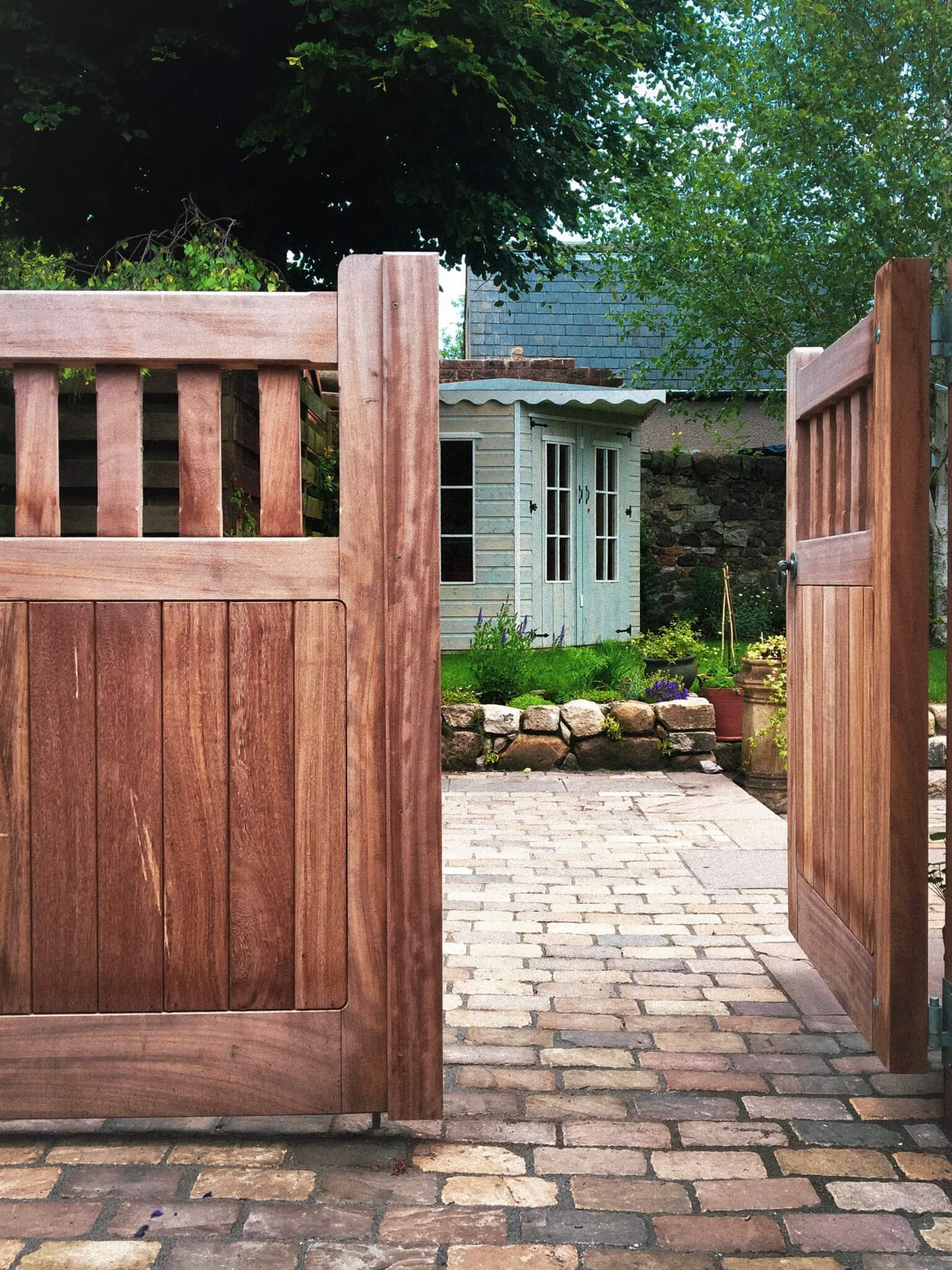 An open wooden gate looking out onto a stone driveway