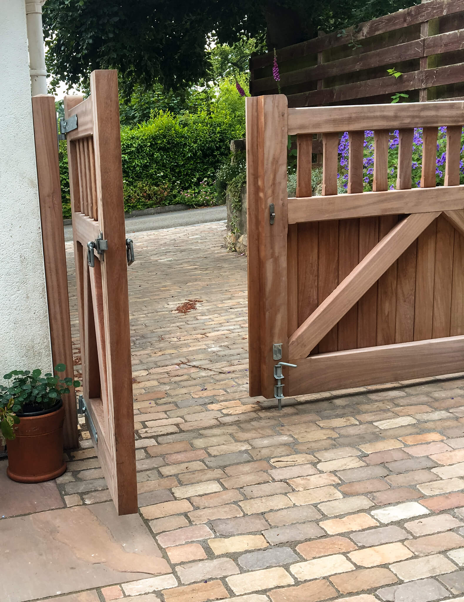 An open wooden gate looking out onto a stone driveway 2
