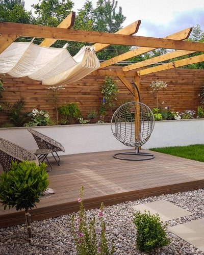 Contemporary Garden with wooden pergola and sliding shade, batten fencing and two seating areas